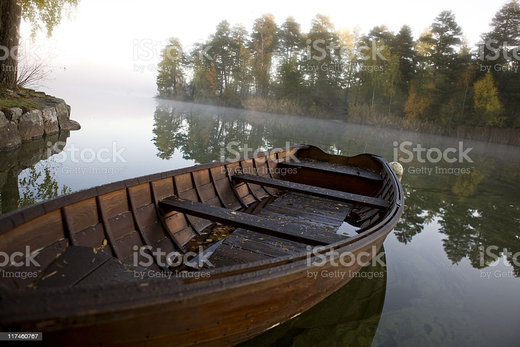 Wooden boat on a misty lake near Stockholm royalty-free stock photo