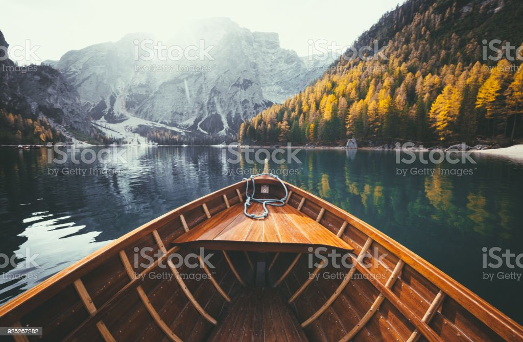 Wooden boat on alpine lake in the Dolomites in fall stock photo