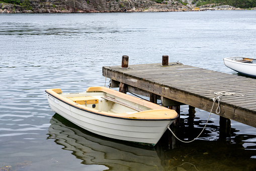 Wooden white boat parking on the wood pier on water with reflection background, Sweden.