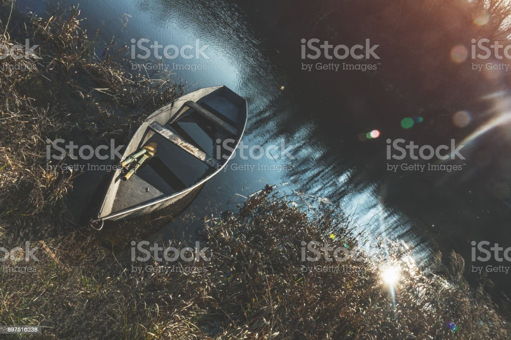 Wooden boat peacefully resting on the water of autumn river at the sunset royalty-free stock photo