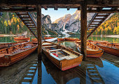 Wooden boats near the house in Braies lake at sunrise in autumn in Dolomites, Italy. Scene with mountains, pier, boat, famous lake, reflection, trees in fall. Travel in Europe. Dolomiti. Italian alps