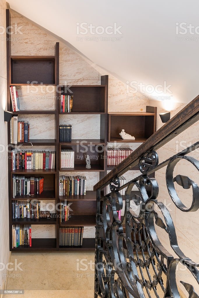 Wooden Bookshelf With Books Near Staircase In Attic Apartment Royalty Free Stock Photo