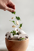 istock Wooden bowl full of mushrooms. Hand pouring parsley and garlic. 1275865909