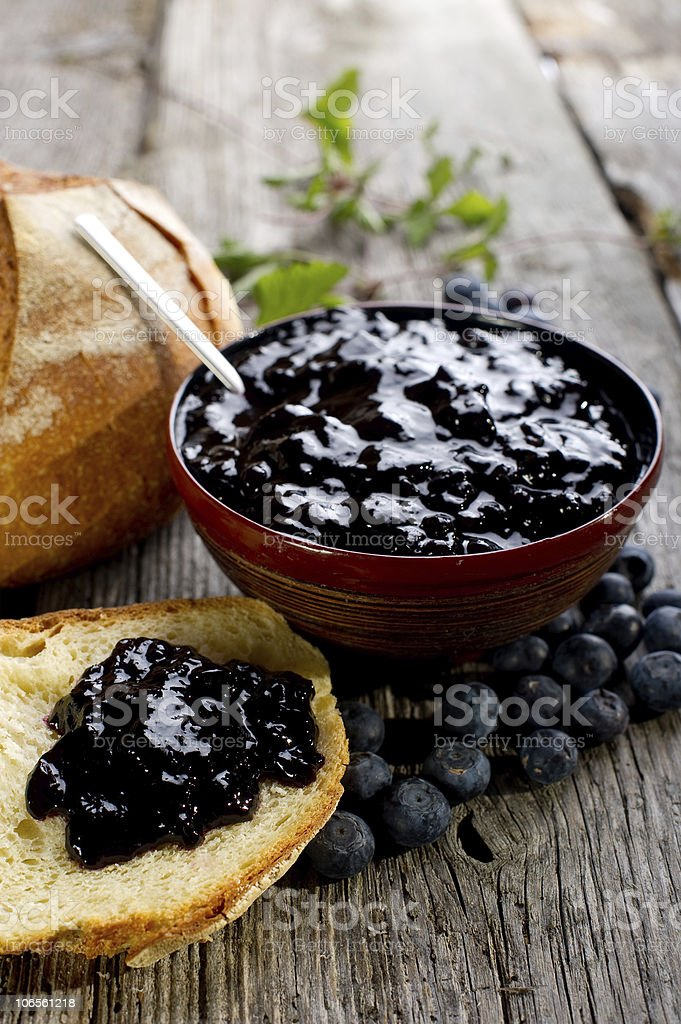 A wooden bowl of blueberry jam with a piece of bread royalty-free stock photo