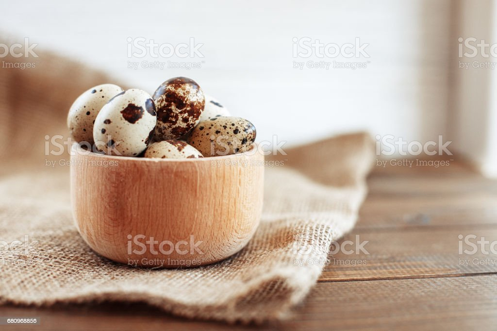 A wooden bowl of quail eggs on the table. The concept of healthy eating and vegetarianism. royalty-free stock photo