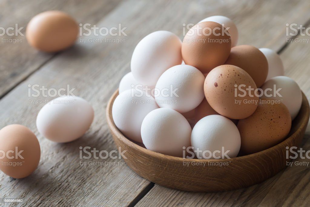 Wooden bowl of raw chicken eggs stock photo