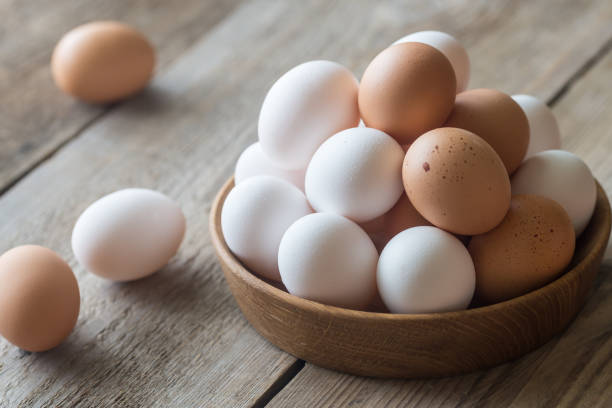 wooden bowl of raw chicken eggs - uovo foto e immagini stock