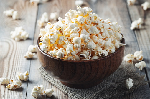 A wooden bowl of salted popcorn at the old wooden table. Dark background. selective focus.