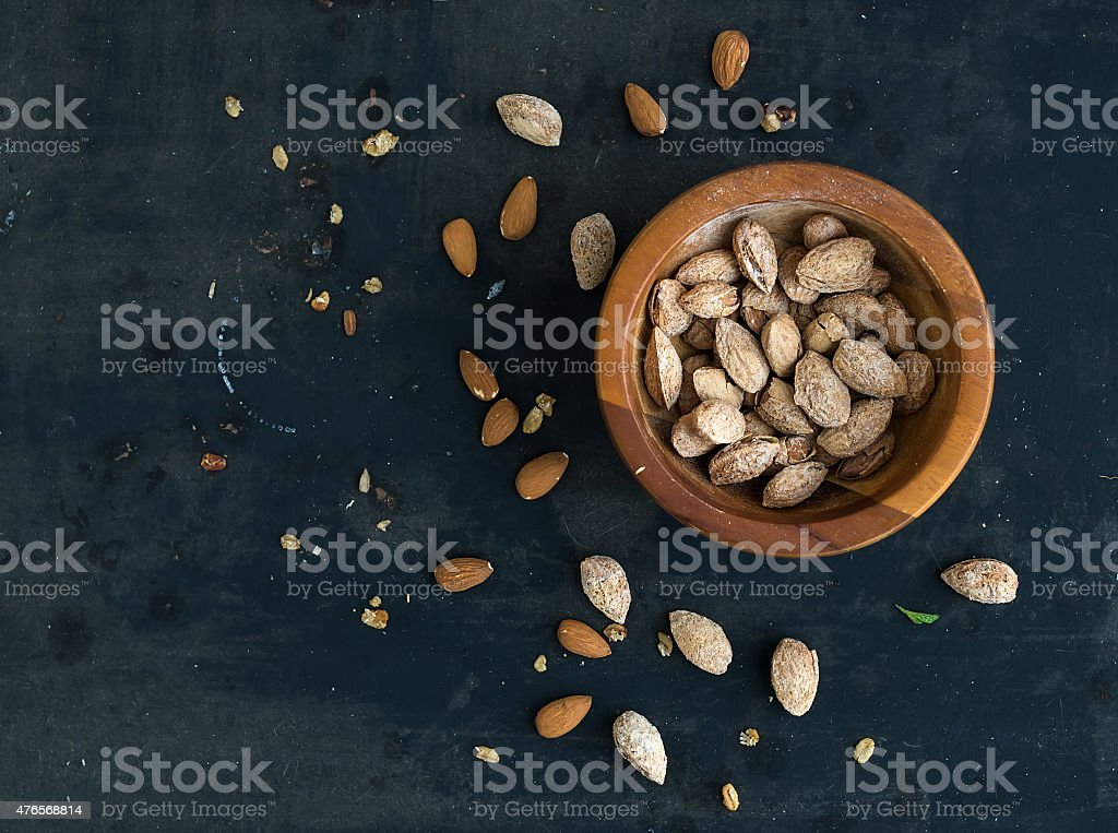 Wooden bowl of salty almond nuts in nutshell grunge dark stock photo