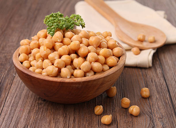 Wooden bowl overflowing with chickpeas topped with parsley chickpea and parsley chick pea stock pictures, royalty-free photos & images