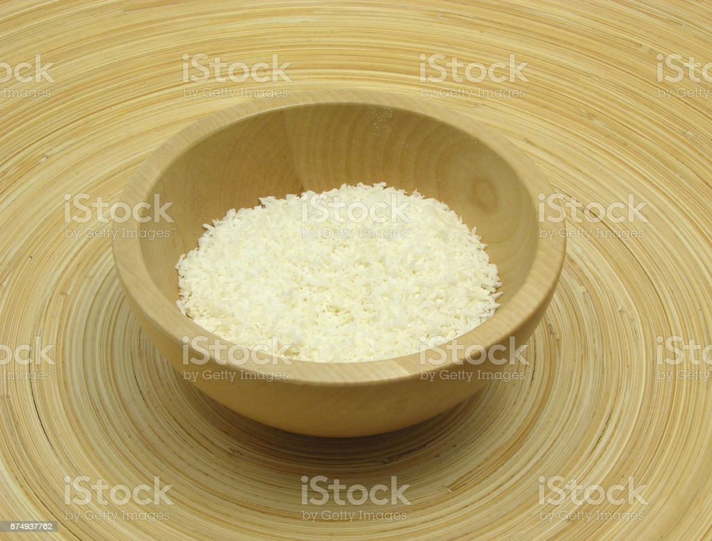 Wooden bowl with coconut flakes on bamboo plate stock photo