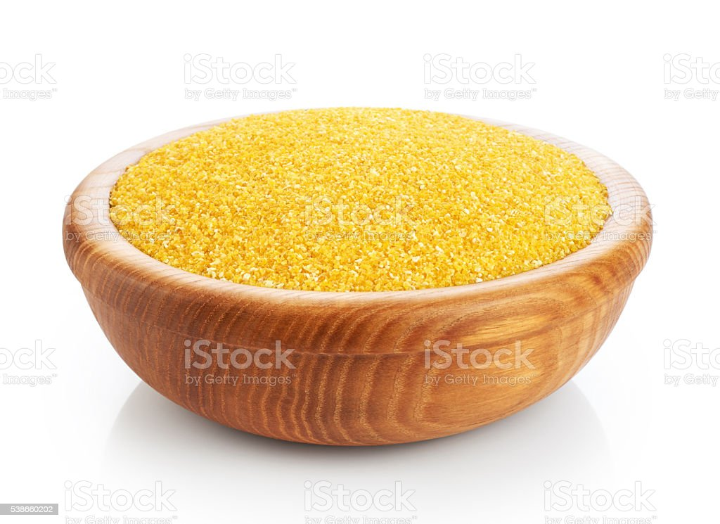 Wooden bowl with corn groats isolated on white background. stock photo