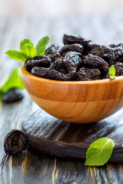 Wooden bowl with dried black plums. stock photo