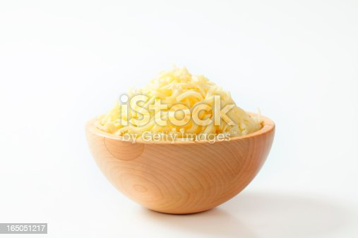Wooden bowl with grated cheese on white background