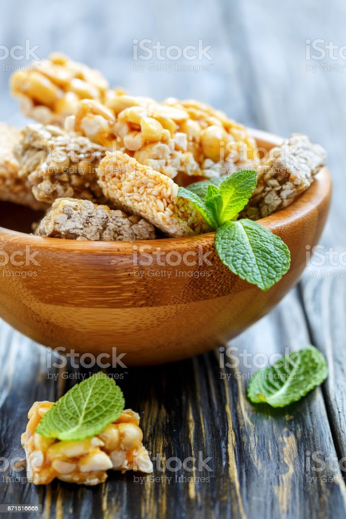 Wooden bowl with honey bars with peanuts, sesame seeds and sunflower seeds. stock photo