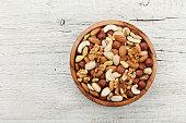 Wooden bowl with nuts. Walnut, pistachios, almonds, hazelnuts. Flat lay.