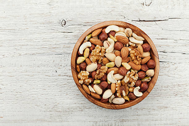 wooden bowl with nuts. walnut, pistachios, almonds, hazelnuts. flat lay. - frutos secos imagens e fotografias de stock