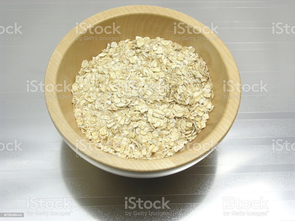 Wooden bowl with oat flakes on reflecting mat stock photo