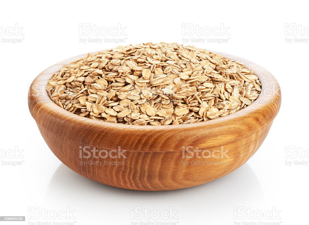 Wooden bowl with oats isolated on white background. stock photo