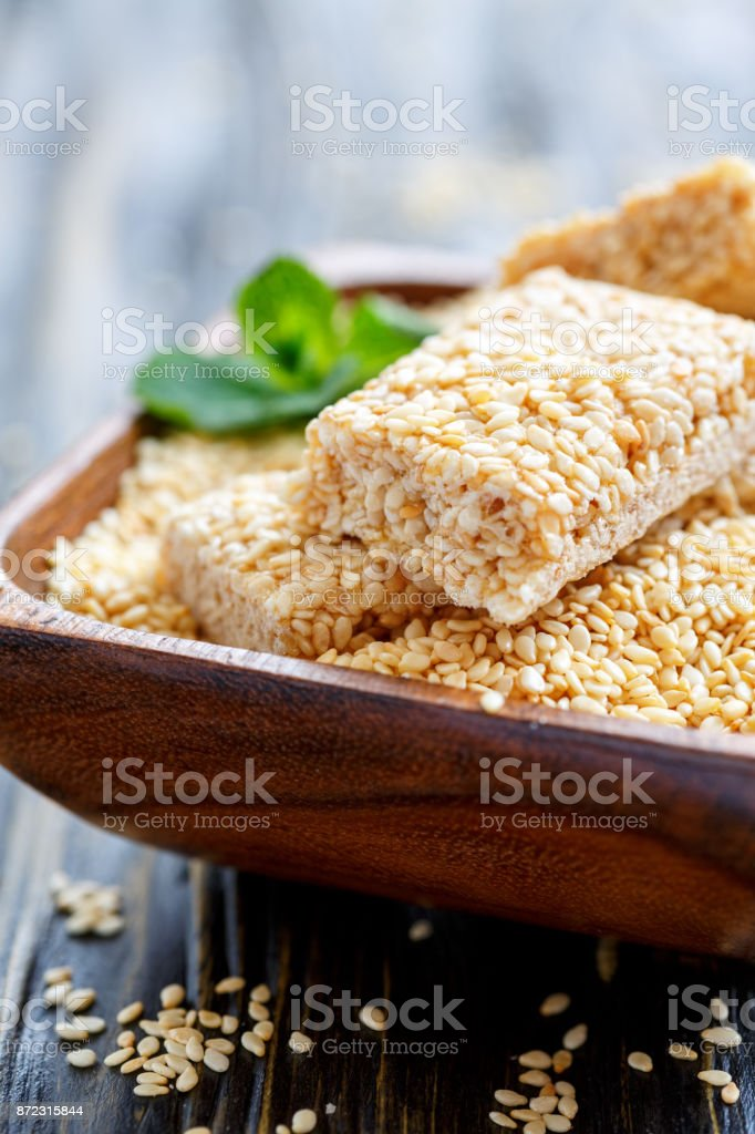Wooden bowl with sesame and honey bars close up. stock photo