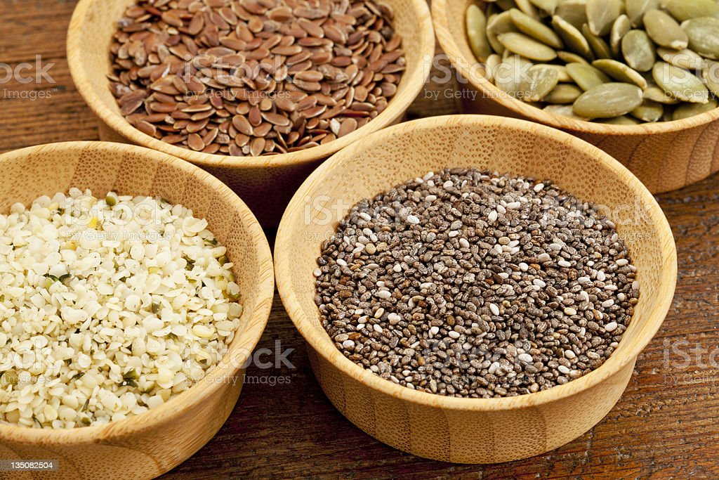 Wooden bowls of chia, hemp, flax and pumpkin seeds stock photo