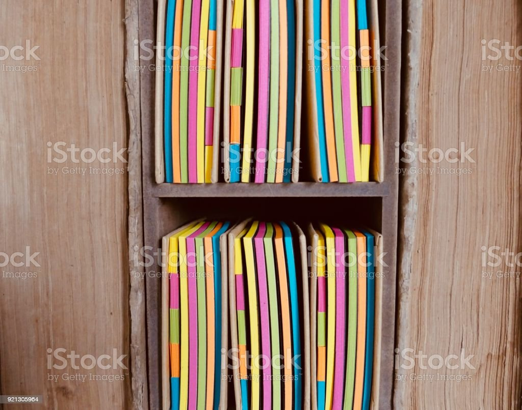 Wooden box filled with colorful adhesives notes between very old book pages stock photo