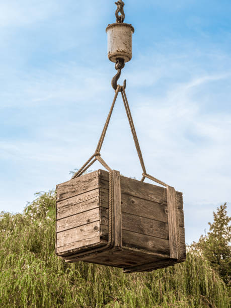 Wooden box hanging on the hook of a crane stock photo