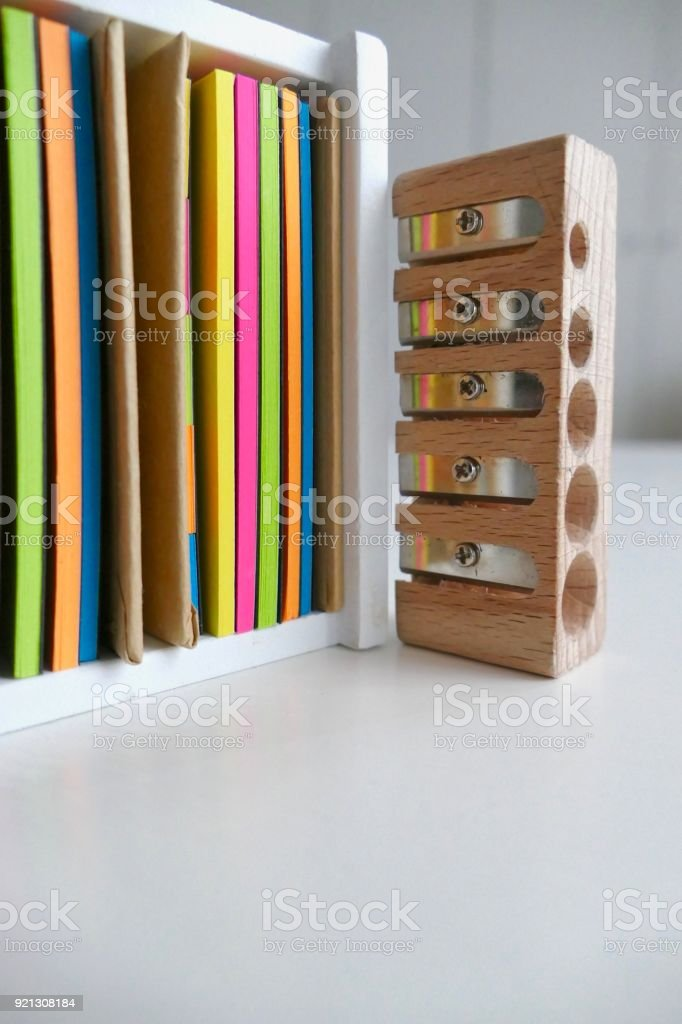 Wooden box on desk filled with colorful adhesives notes with a pencil sharpener stock photo