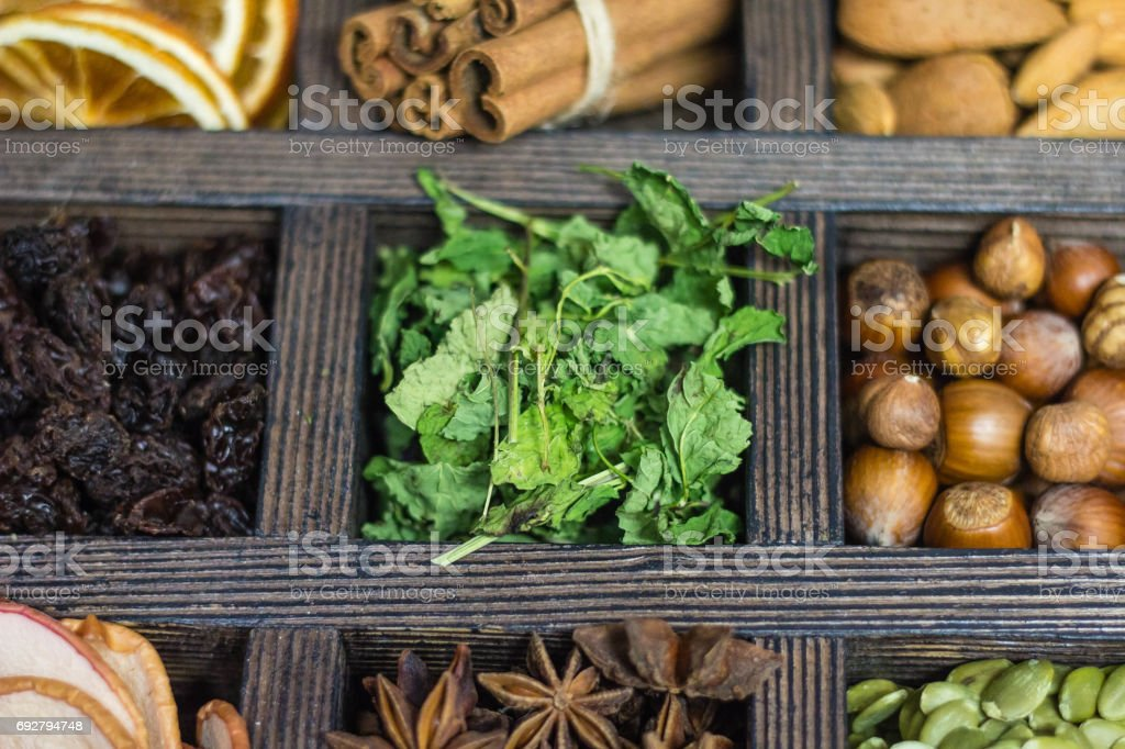 wooden box with nuts, spices and dried fruits, mint on wooden background stock photo