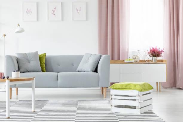 holzkiste mit olivgrünen kissen auf gestreiften teppich in hellen skandinavischen wohnzimmer mit grauen sofa und couchtisch, echtes foto - oliven wohnzimmer stock-fotos und bilder