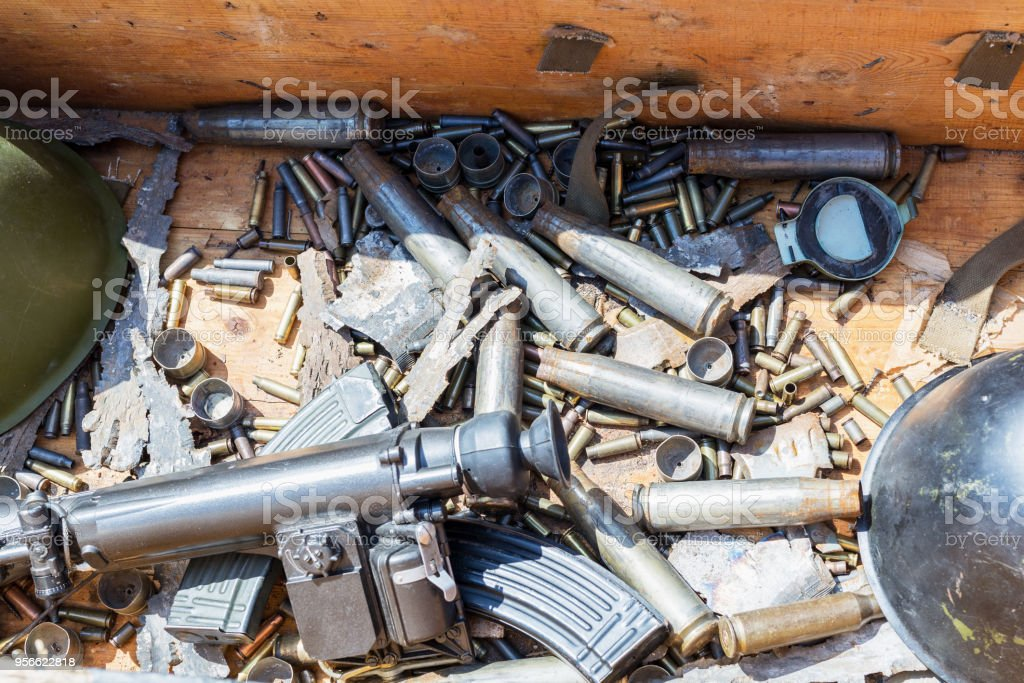 Wooden box with used war ammunition. Bullets, shells helmets, magazine and sniper sight. Battle souvenirs stock photo