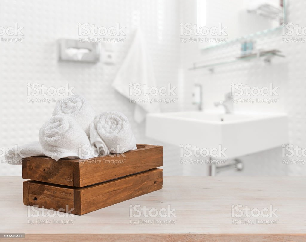 Wooden box with white spa towels on blurred bathroom background - foto de acervo