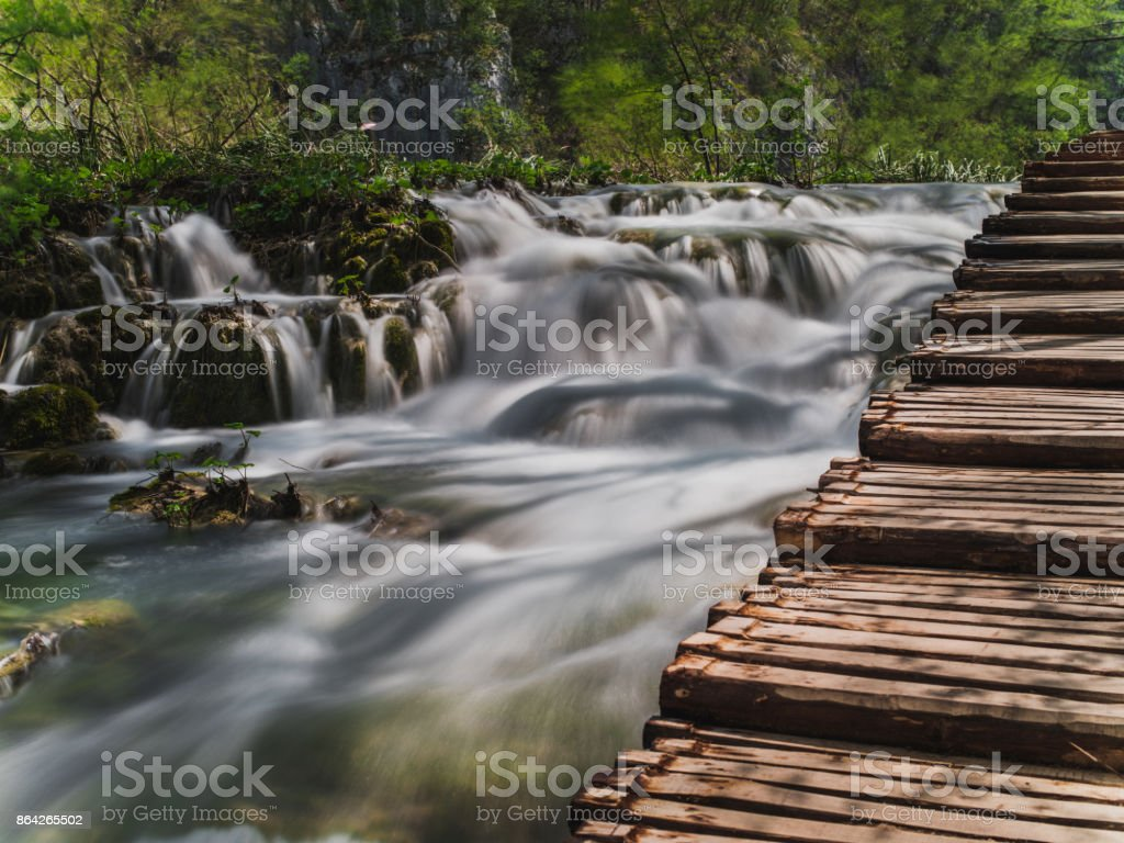 wooden bridge above waterfalls royalty-free stock photo