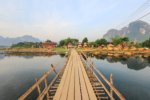 holzbrücke auf fluss nam song in vang vieng, laos - vang vieng stock-fotos und bilder