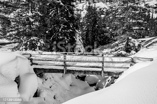 wooden bridge covered with snow on the trails in the dolomites in Trentino Alto Adige, Italy