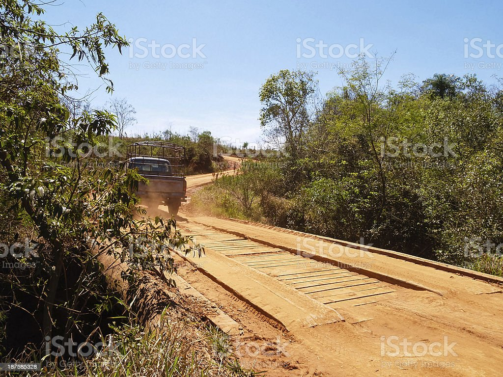 Wooden bridge, dusty dirt road. Roads in Paraguay, South America stock photo
