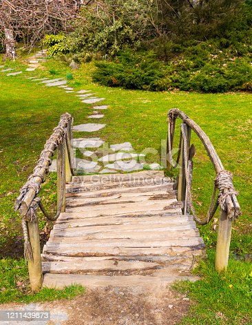 Handmade wooden arched old small bridge on grass in botanical garden.