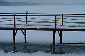 Photography of the  wooden bridge in the winter day. Snowy Russian countryside. Blizzard. Snow-covered Istra water reservoir. Concept of the beauty in nature.