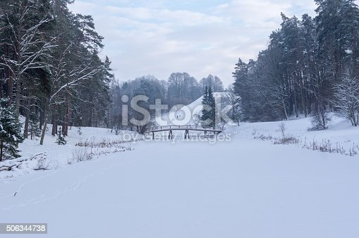Tourist path. Wooden bridge over a small winter, the frozen river forest