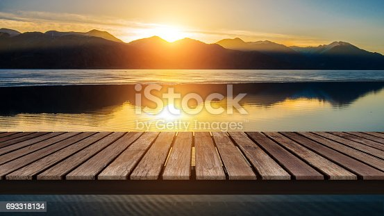 istock Wooden bridge on the lake with a reflection of sunset on the snow mountain 693318134