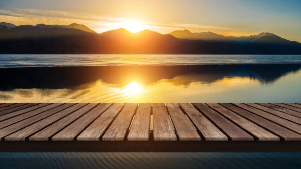 Wooden bridge on the lake with a reflection of sunset on the snow mountain stock photo