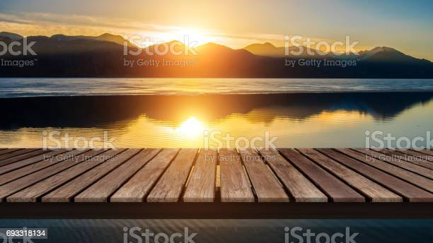 Photo of Wooden bridge on the lake with a reflection of sunset on the snow mountain