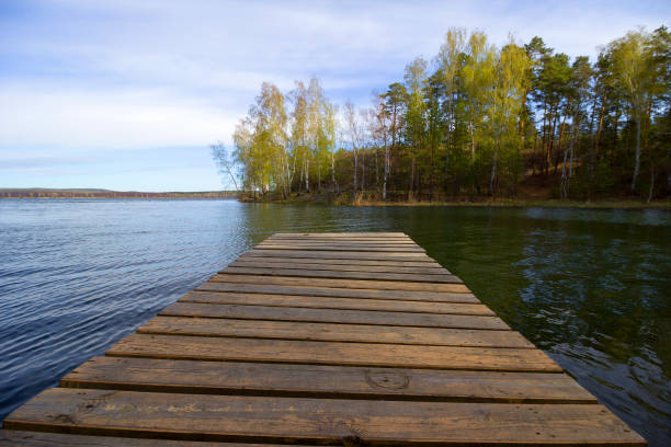 wooden bridge over a tranquil lake - lakeshore stock photos and pictures