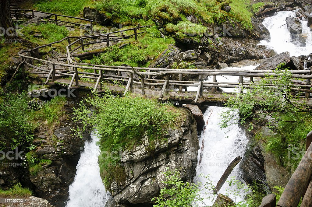 Wooden bridge over Saent waterfalls in the Italian mountains royalty-free stock photo