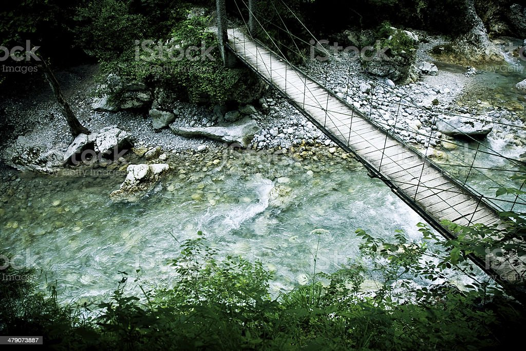 Wooden bridge over the mountain river royalty-free stock photo