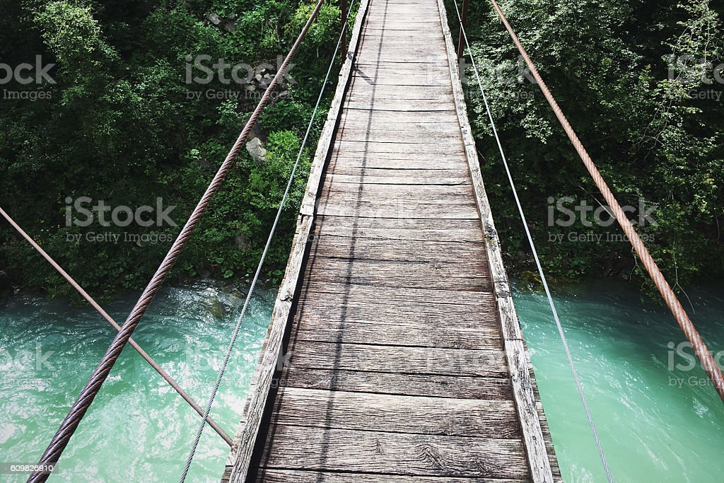 Wooden bridge over the mountain river stock photo