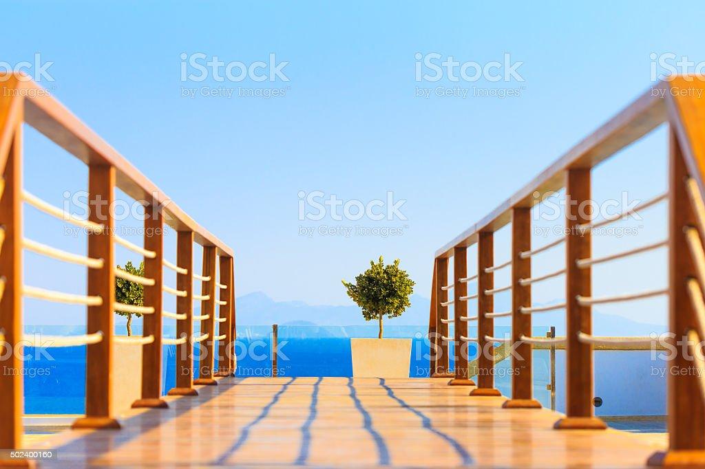 Hölzerne Brücke über den pool mit blauen Meer im Hintergrund – Foto