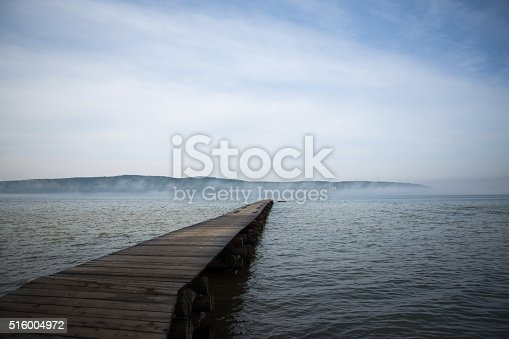 Morning at the lake. Beautiful old wooden pier and forest hill in background