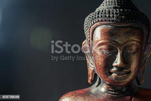 Wooden bronze buddha on black blurred background close up