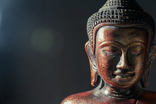 istock Wooden bronze buddha on black blurred background close up 826799048